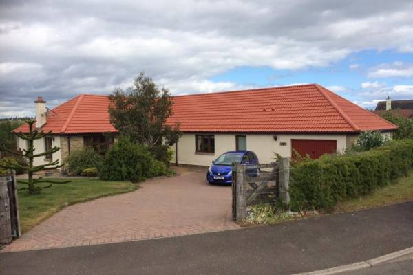house with red roof and car in driveway