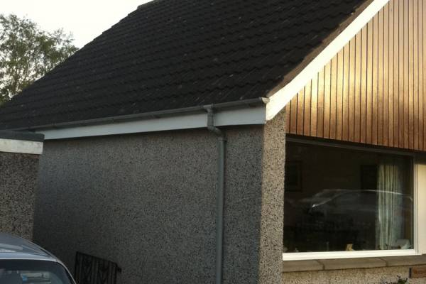 brown tiled house with pebble render